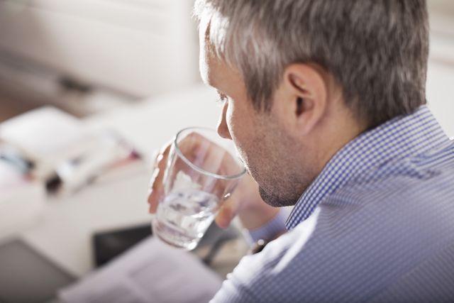 mature businessman drinking water