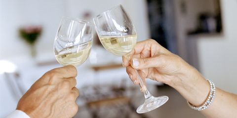Mature couple clinking champagne flutes, close-up wine
