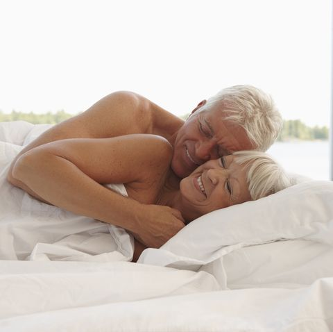 mature couple cuddling in bed
