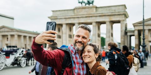 A Mature Couple Take A Selfie Together In Front Of Brandenburg Gate in Berlin