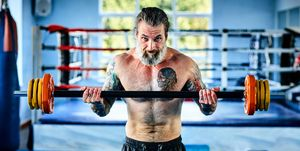 Mature male boxer working out with barbell at gym