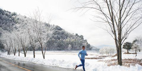 Mature male runner running on road in winter, Lake Kawaguchiko, Mount Fuji, Japan