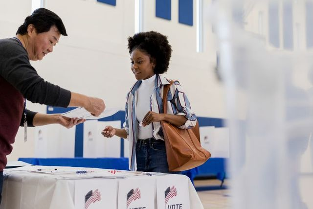 mature male volunteer explains voting document to young woman