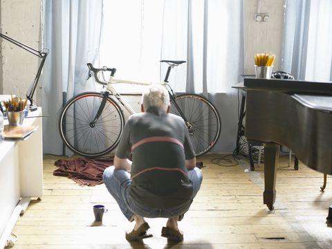 mature man crouching down, looking at bicycle, rear view