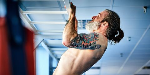 Mature man doing pull ups in the gym