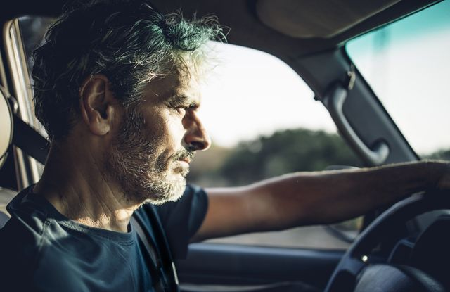 mature man driving at sunset