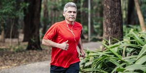 Mature man jogging in woods with earphones