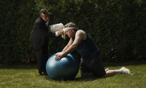 Mature man kneeling on lawn, leaning on exercise ball, butler wiping his forehead