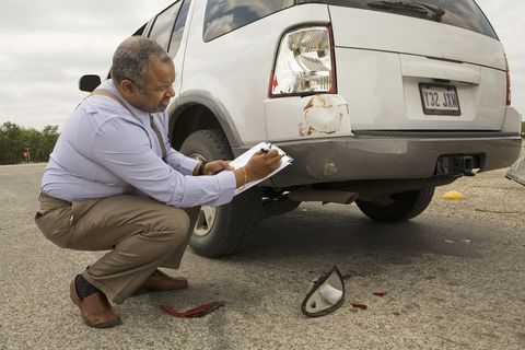 Mature man writing on clipboard by crashed car