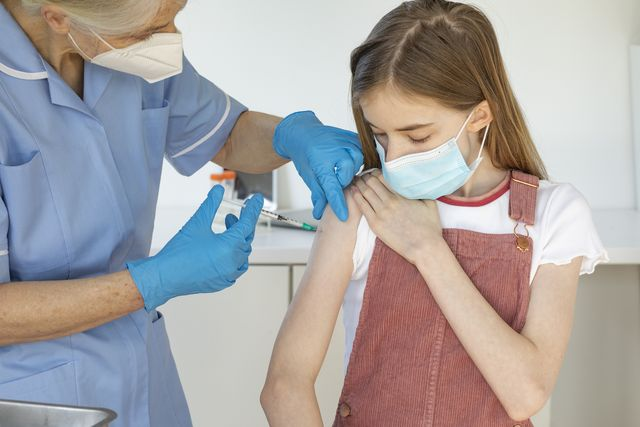 mature nurse giving out covid vaccine