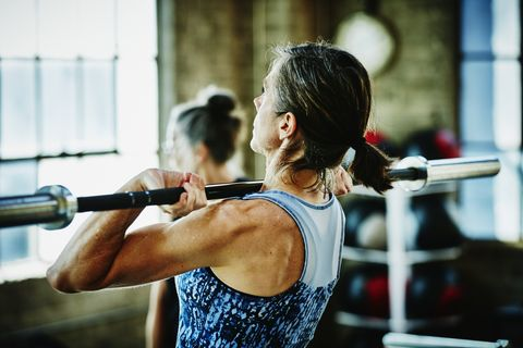 Mature woman doing barbell lifts during workout