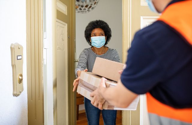 mature woman getting package from delivery person during pandemic