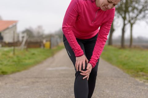 Mature Woman Holding Knee On Road