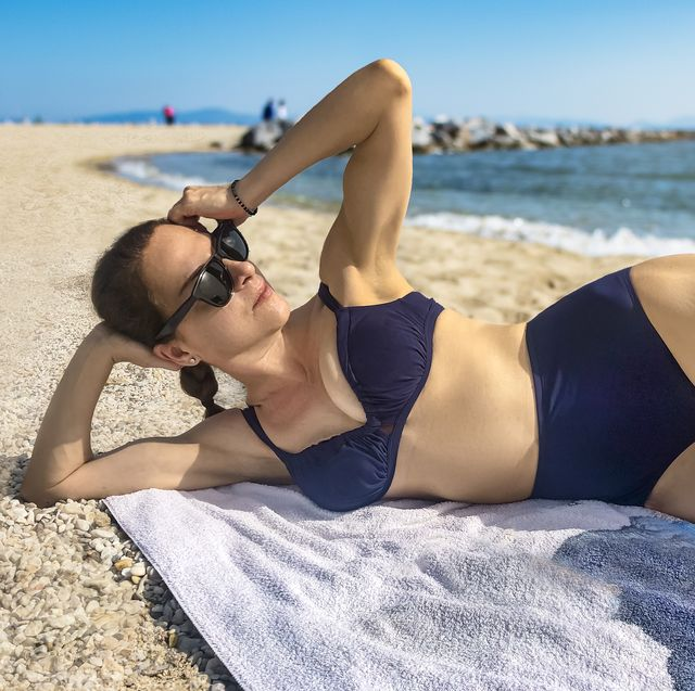 mature woman laying on the beach wearing sunglasses and a high waist retro swimsuit looking away