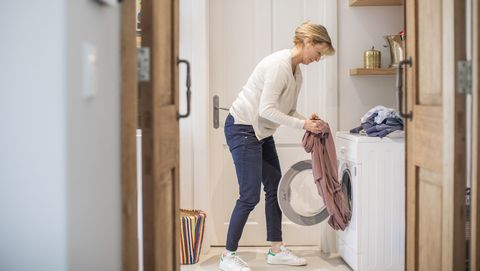 Mature woman loading clothes in washing machine