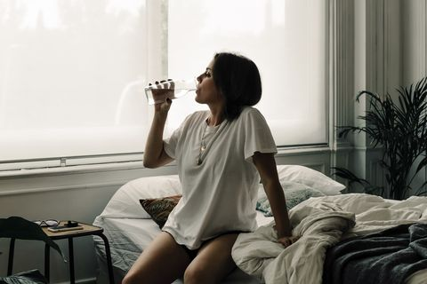 mature woman sitting on bed in the morning drinking water