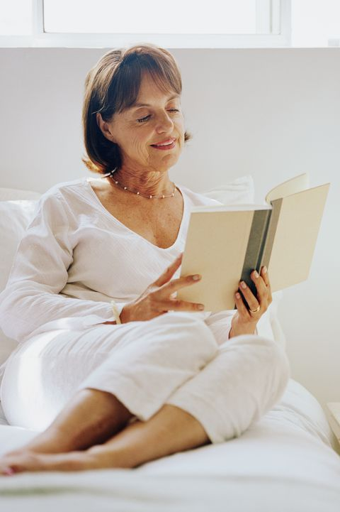 virtual happy hour ideas -  Mature woman sitting on bed, reading book