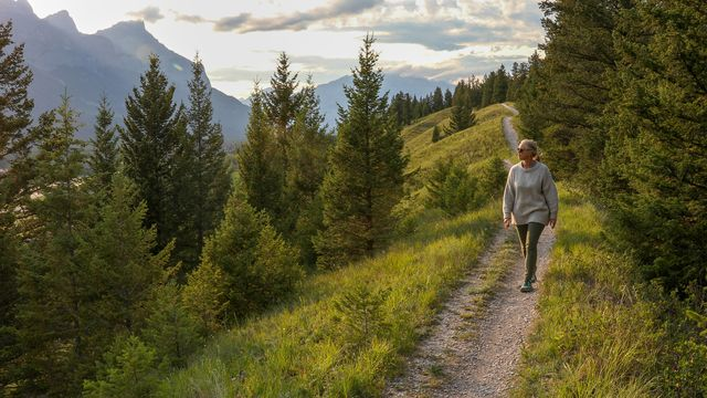 mature woman walks down trail in the morning