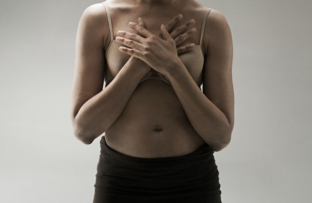 mature woman wearing pink bra with hands covering chest
