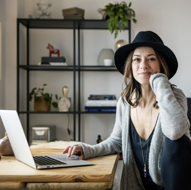 mature woman with hat, sitting at home, using laptop