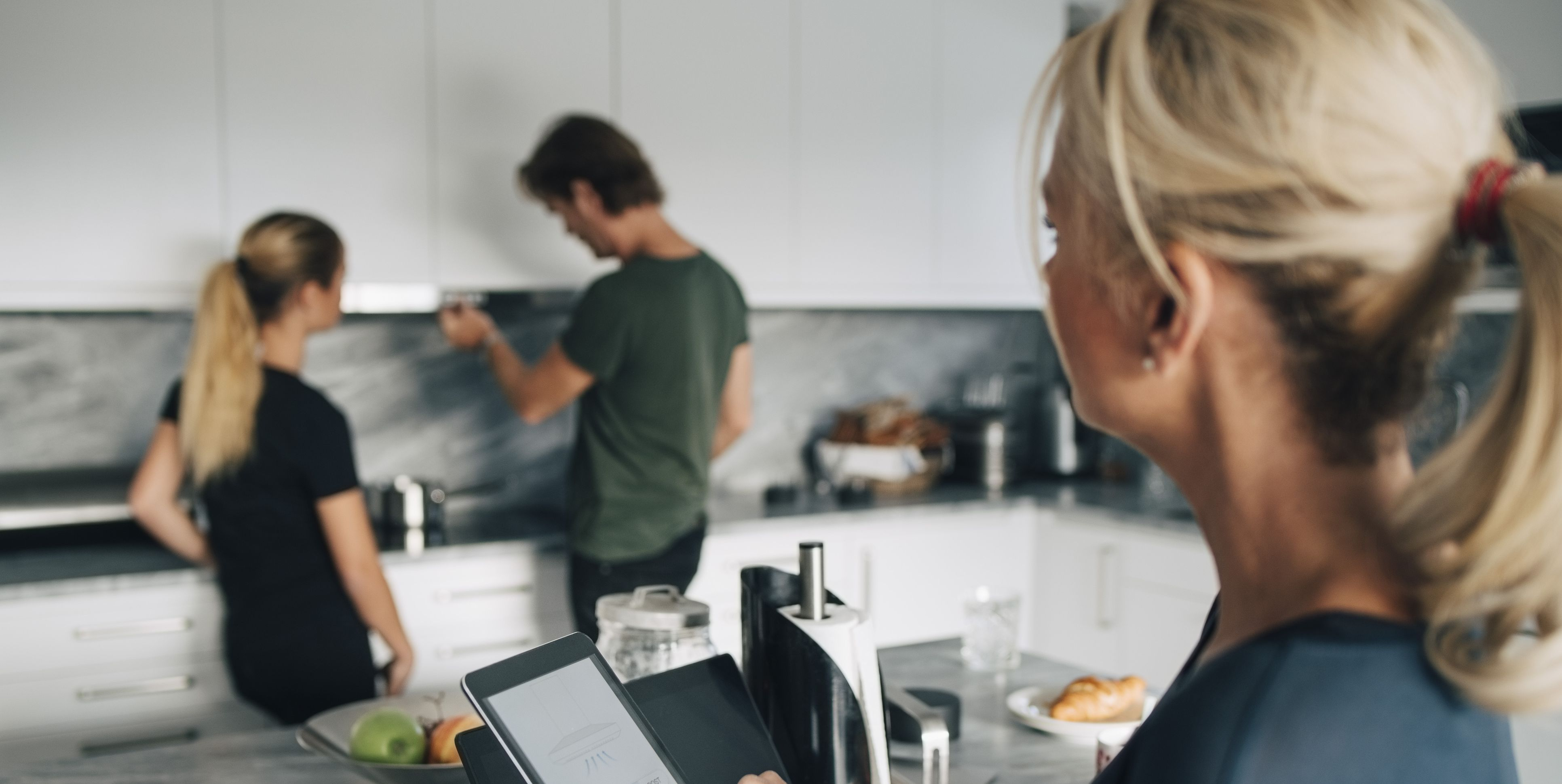 Mature woman with technologies looking at man and daughter standing in kitchen