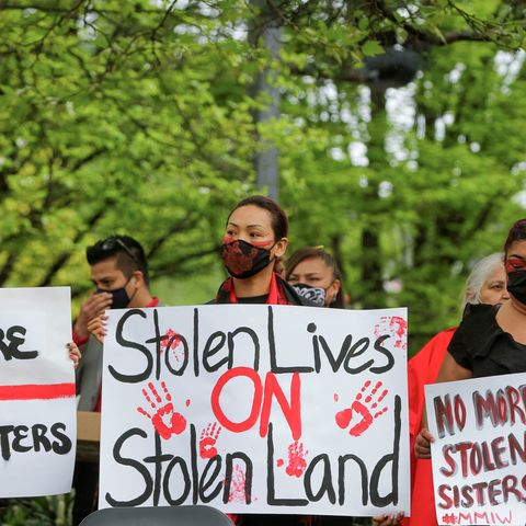 woman with her face painted holding a sign that says stolen lives on stolen lands