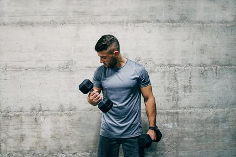 Man standing in front of wall and lifting dumbbells. How many sets is good for biceps?