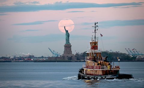 the may supermoon in the sky behind the statue of liberty