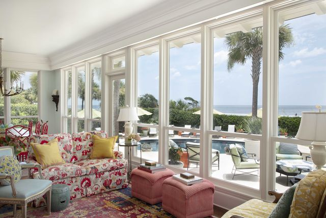 screened porch with floral couch and pink ottomans, overlooking pool