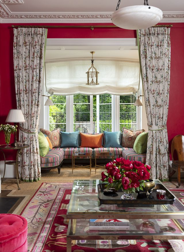 in the living room a convivial window seat overlooks an emerald and white back garden and a banquette has striped fabric