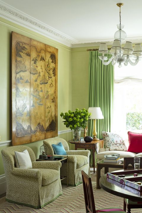 a pair of syrie maugham chairs in the sitting room are covered in a panther print velvet and a 1950s chinoiserie panel hangs above