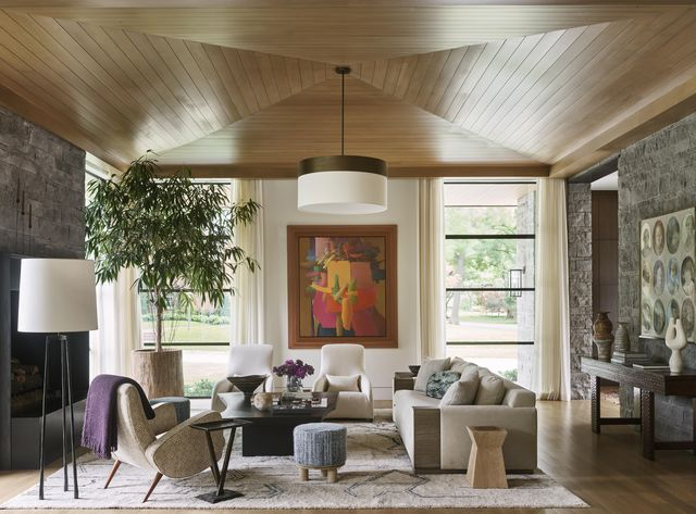 a sofa and chairs in a large living room with a paneled wood ceiling