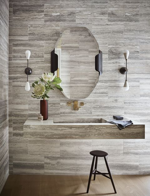 in the powder room, travertine stone extends to a floating custom sink