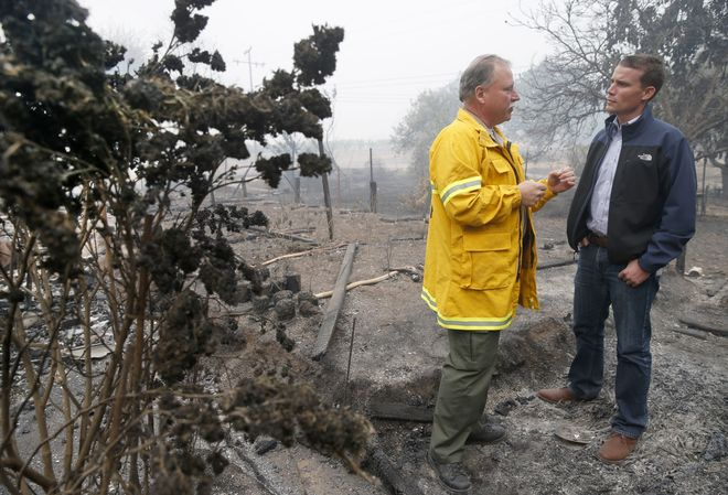 Mendocino Co. Sheriff Tom Allman briefs state Sen.MikeMcGuireon Monday morning's fire next to singed marijuana plants (left) that were growing at a home destroyed by fire on East Road in Redwood Valley, Calif. on Tuesday Oct. 10, 2017. Authorities have reported at least three people have died and 50 residences have been destroyed by the Redwood Complex Fire.