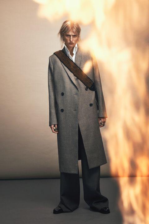 Suit, Standing, Formal wear, Overcoat, Human, Coat, Outerwear, Trench coat, Tuxedo, Fictional character,
