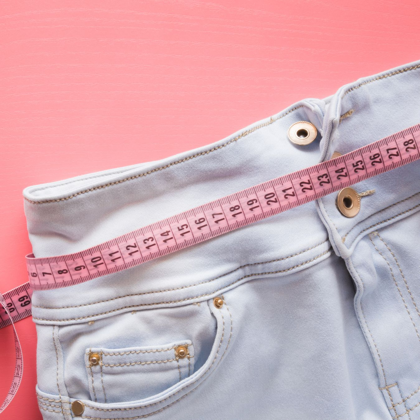Measure tape with light blue jeans on the pastel pink background. Women diet. Mock up for healthy lifestyle, body slimming, weight loss or dressmaker's offer or other ideas. Empty place for text.