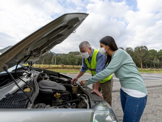 mechanic assisting woman having problems with her car on the road and wearing a facemask