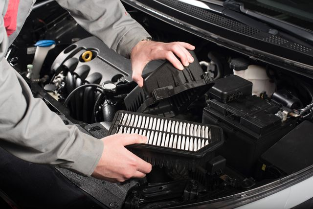 mechanic changing the air filter on a car