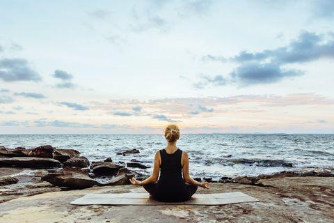 Mujer meditandofrente al mar