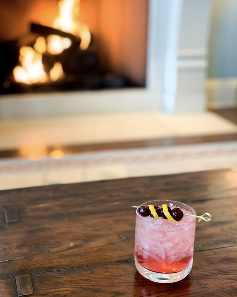mule, ginger beer cocktail, lemon peel with olives on top of red drink with ice, pictured in front of a fire