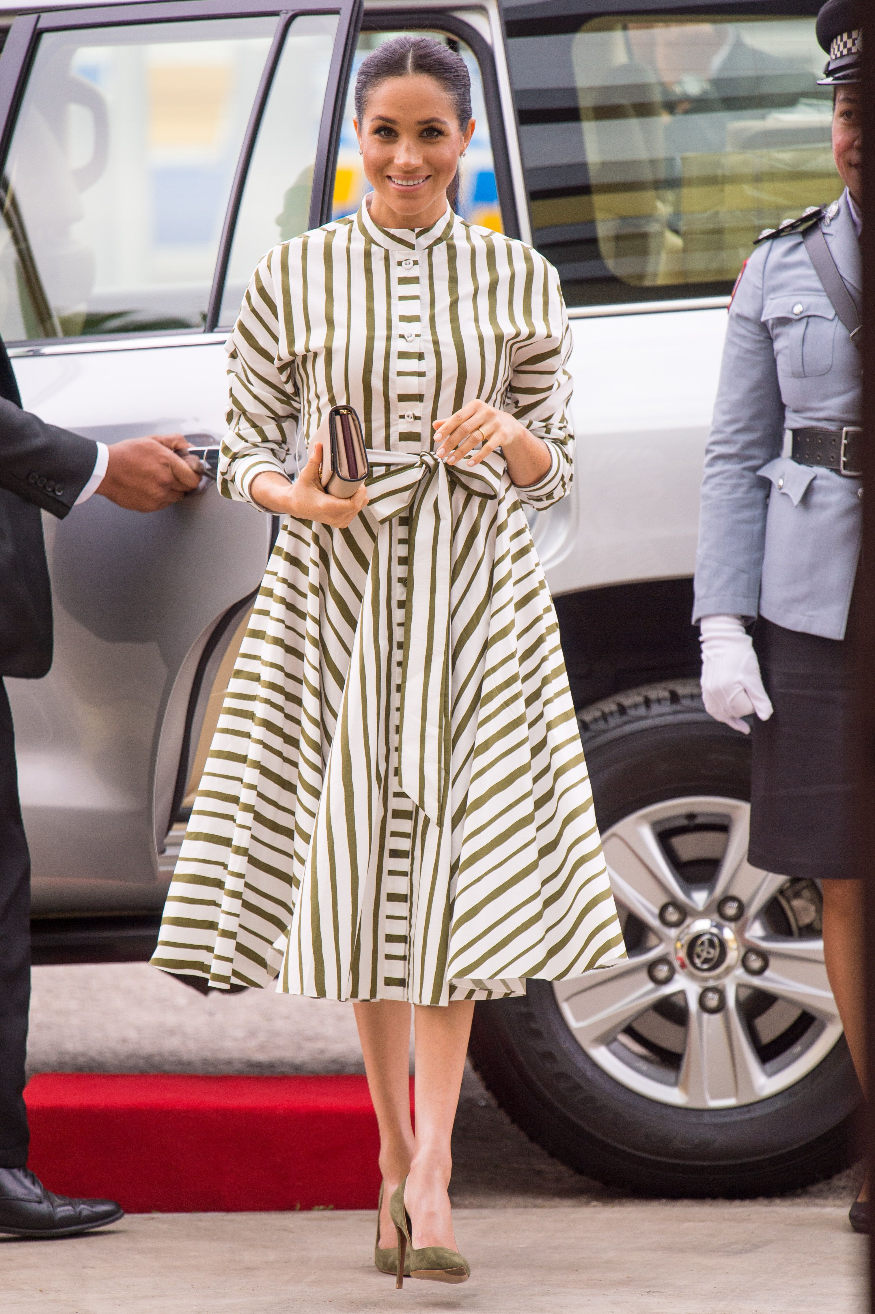 Meghan kicked off her second day in Tonga wearing a striped dress by Martin Grant. She finished her outfit off with a clutch by Prada and green heels.