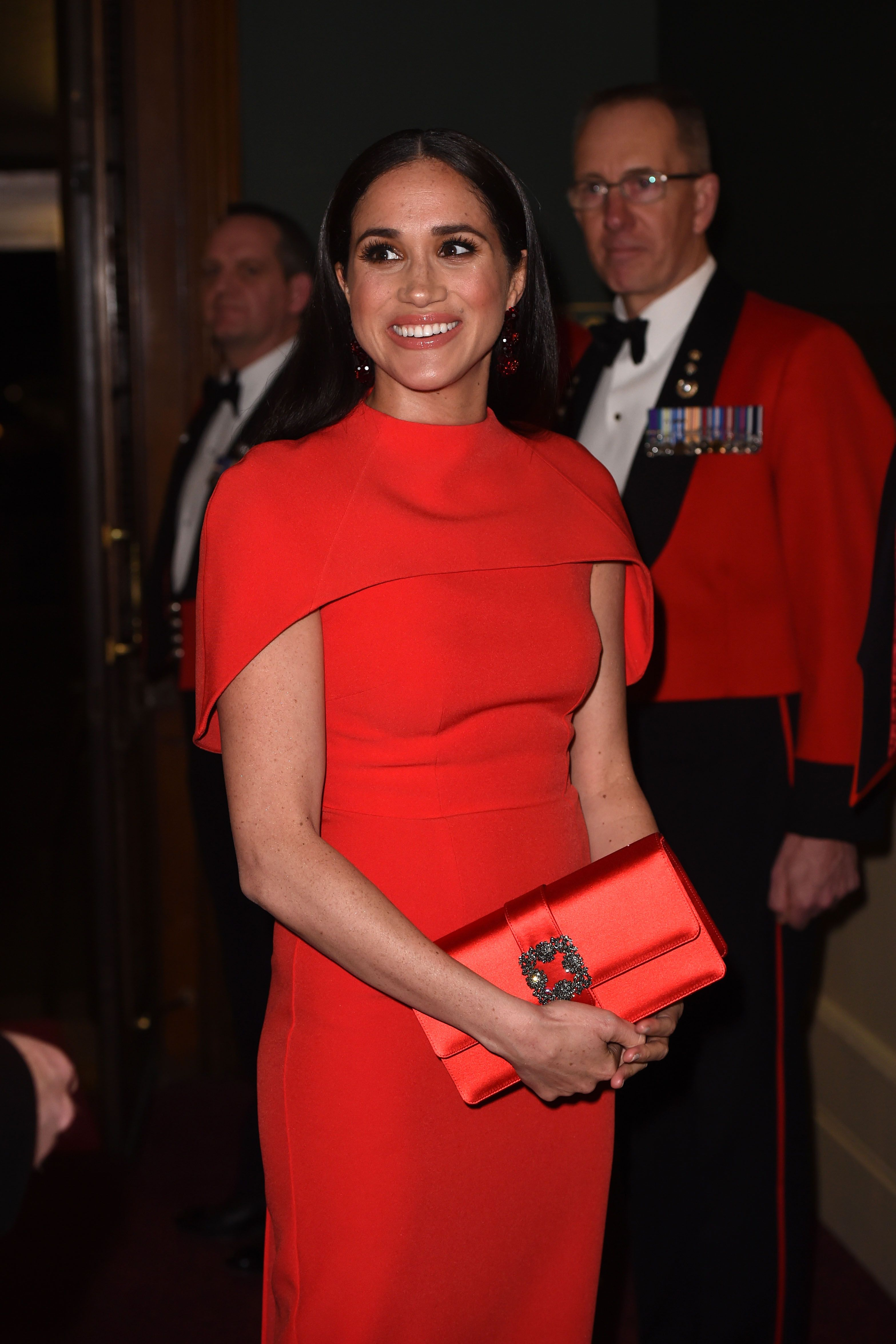 meghan markle in a red cape dress at the mountbatten festival of music meghan markle in a red cape dress at