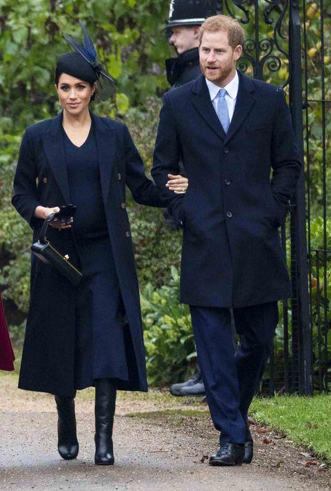 Clothing, Uniform, Standing, Outerwear, Coat, Academic dress, Headgear, Overcoat, Formal wear, Suit,