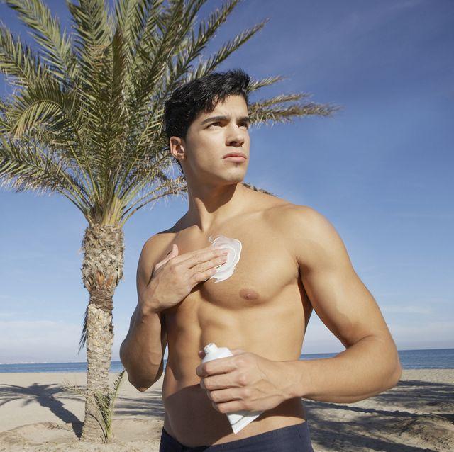 un hombre se aplica crema after sun en el pecho después de correr en la playa
