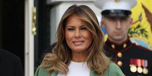 Melania Trump con falda de print serpiente, jersey fino blanco y abrigo aguamarina