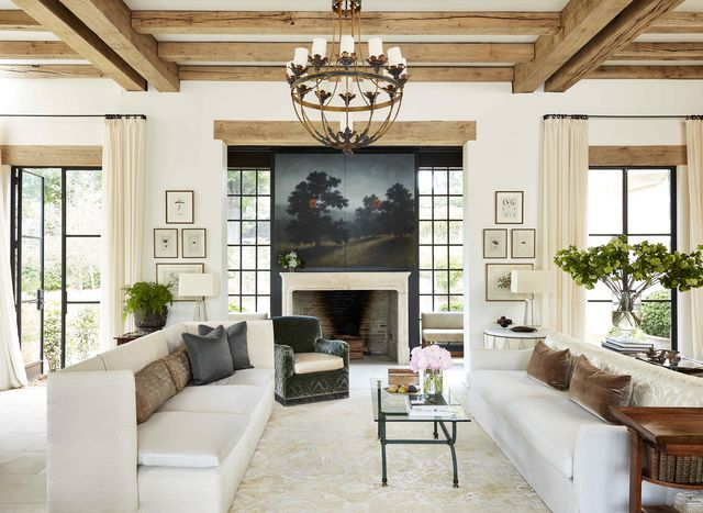 two sofas face each other in a large living space with a landscape painting hanging above the fireplace