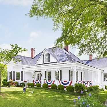 a white farmhouse is decorated with red white and blue bunting that hangs on the porch