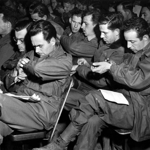 men of a us troop carrier group, 1st allied airborne army, synchronize their watches during a briefing preceeding the droping of paratroopers and gliders troops east of the rhine river