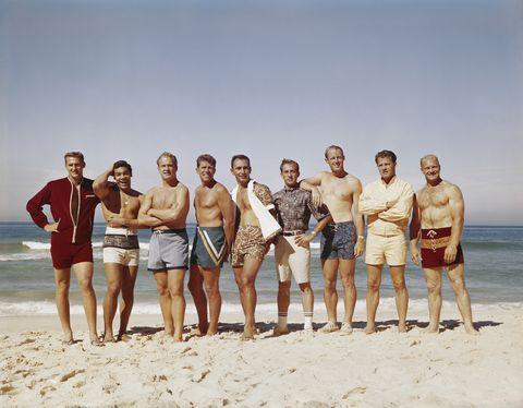 Men standing on beach, smiling, portrait