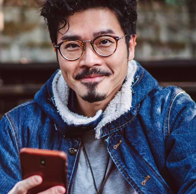 man with phone wearing glasses and jean jacket sitting on steps